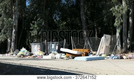 Household Waste Dumped Next To Overflowing Containers In Forest Lay-by