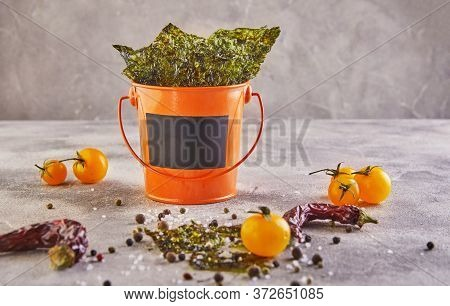 Crispy Nori Seaweed With Cherry Tomatoes And In An Orange Bucket On Gray Concrete. Japanese Food Nor