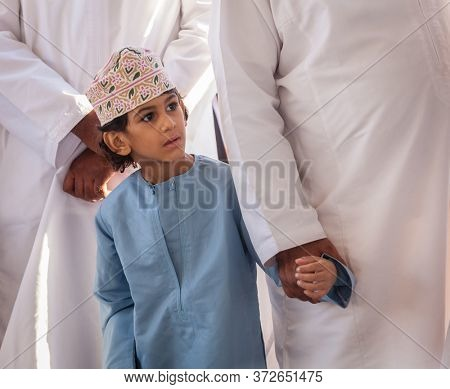 Nizwa, Oman, December 2, 2016: Portrait of a local boy in traditional clothes at the Friday goat market in Nizwa, Oman
