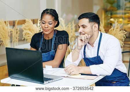 Young Multi-ethnic Cafe Owners Reading E-mails From Food Suppliers On Laptop Screen