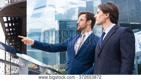 Teamwork and business concept. Confident businesspersons having conversation about banking and financial markets in front of office building.