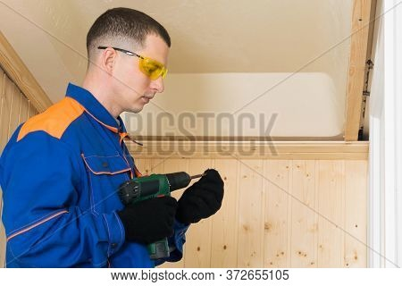 Master In Blue Special Clothes Holds A Screwdriver And Changes The Nozzle