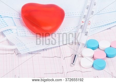 Concept Of Protective Medical Masks, Thermometer For Measuring Temperature, Vitamins And Red Heart O