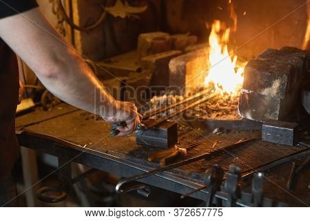 Blacksmith Manually Forging On Iron On Anvil At Forge. Treatment Of Molten Metal Close-up.