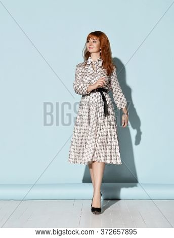 Young Beautiful Smiling Relaxed Red-haired Woman In Elegant Light Dress And Black High Heel Shoes Is