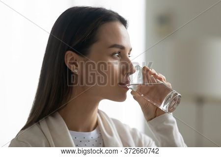 Beautiful Woman Holding Glass Drinking Water Looking In Distance