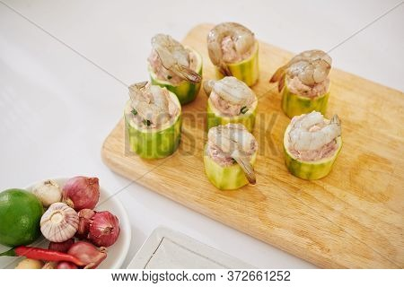 Wooden Board With Zuccini Pieces Filled With Ground Meat Decorated With Shrimps