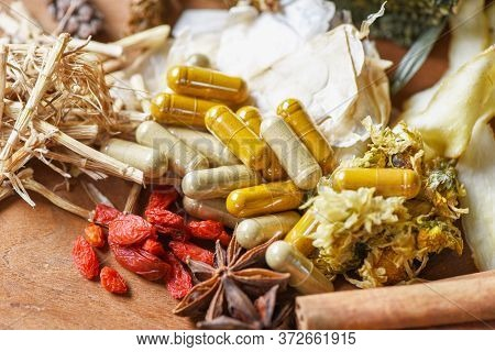Herbal Medicine Capsules And Dried Herb From Nature Non-toxic Organic Product On Wooden Background /