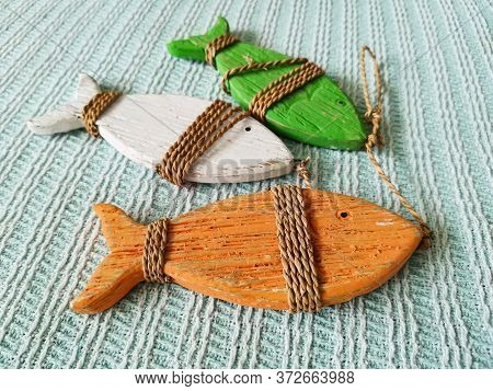 Three Wooden Decorative Fish Of Red, Green And White, Tied With Twine. Interior Items In Country Sty