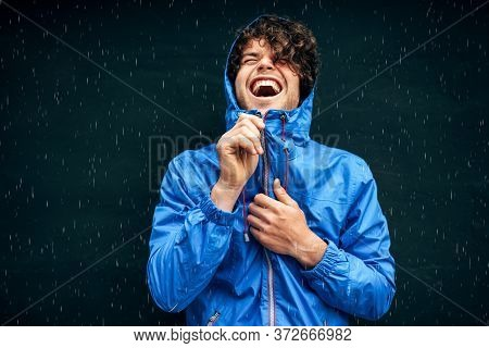 Happy Man Smiling Broadly, Wearing Blue Raincoat During The Rain Outside. Handsome Male In Blue Rain