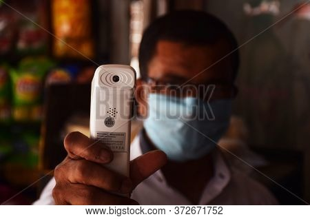 Delhi - India June 22 2020 An Indian Shopkeeper Screening A Customer With His Thermal Scanner Or Gun