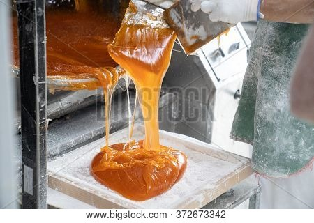 A Worker Confectionary Factory For A  Marmalade Or Caramel On The Scales For Rolling.