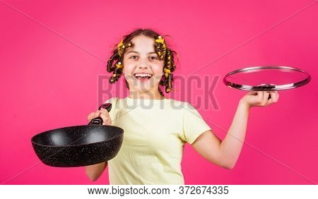 Small Girl Housewife Cooking At Kitchen. Portrait Of Cute Little Girl With Pan. Funny Little Housewi