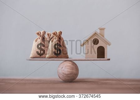 Us Dollar Hessian Bags With House Paper Model On A Wood Balance Scale. Home Loan, Reverse Mortgage C