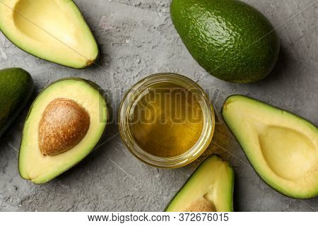Ripe Fresh Avocado And Oil On Gray Background, Top View