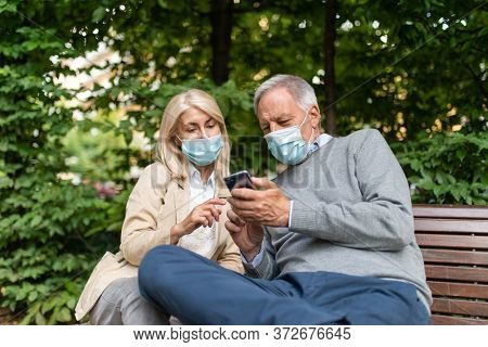 Mature couple using a cellphone in a park during Coronavirus pandemic