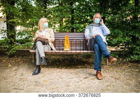 Social distancing and separation concept, coronavirus prevention while sitting on a bench in a park