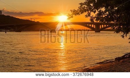 Arch Bridge Across The River And Setting Sun Over It In City. Metro Bridge And Dnieper River, Kyiv,