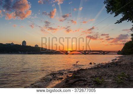 Arch Bridge Over The River In City At Sunset. Metro Bridge Across Dnieper River, Kyiv, Ukraine