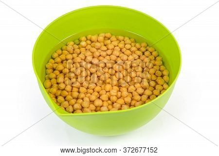 Uncooked Yellow Chickpeas Soaked In Cold Water In The Green Plastic Kitchen Bowl For Subsequent Fast