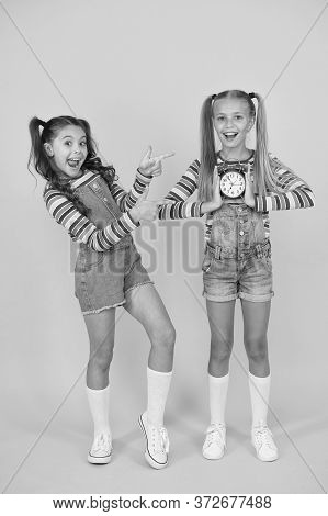 Children Break Concept. Two Cheerful Girls Hold Alarm Clock. Back To School. Summertime. Discipline