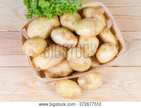 Raw Washed Yellow Young Potatoes With Unpeeled Thin Skin In The Small Wooden Basket And Beside On Th