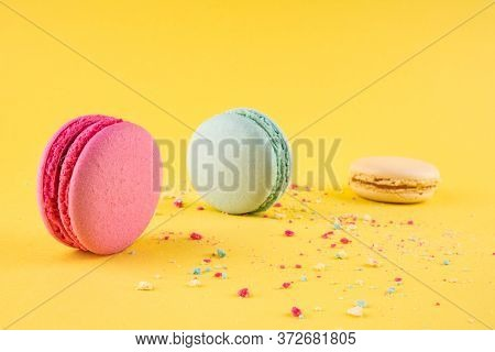 Three Colorful Crushed Macarons Dessert Lying On Colorful Crumbs, Flat Lay Style, Concept For Holida