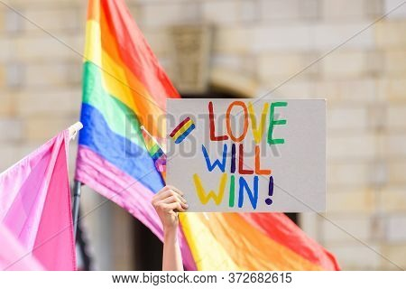 Human Hand Hold A Poster With The Inscription About Love Will Win And Lgbt Rainbow Flag On A Backgro
