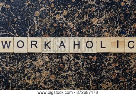 Word Workaholic From Wooden Letters In Black Font On A Brown Shabby Wall With A Pattern