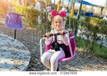 Little Cute Adorable Caucasian Blond School Girl Enjoy Having Fun Sitting And Riding Old Chain Swing