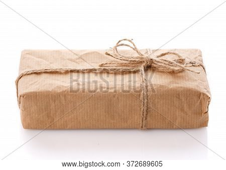 Parcel Wrapped In Brown Kraft Paper Isolated On White Background.