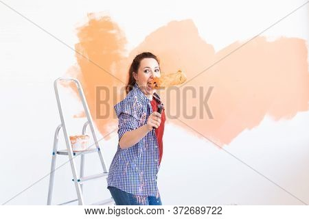 Dancing Funny Woman Painting Wall In Her New Apartment. Renovation And Redecoration Concept.