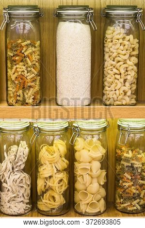 Different Types Of Raw Pasta Stored In Closed Glass Jars On The Shelves. Showcase Decoration. Fettuc