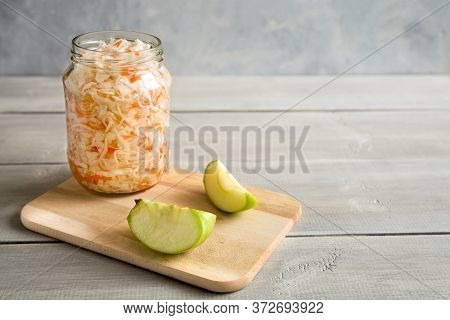 Homemade Sauerkraut In Glass Jar On Wooden, White Background. Next To It Are Slices Of Apple. Fermen