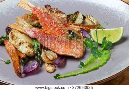 Sea Bass With Grilled Vegetables, Carrots, Garlic, Cauliflower, Asparagus And Decorated Peas Microgr