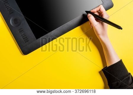 Cropped View Of Designer Holding Modern Stylus Near Drawing Tablet With Blank Screen On Yellow
