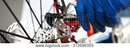 Gloved Repairman Hand Adjusts Tool On Bicycle. Preparation For New Bike Season During Quarantine. Re