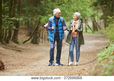 Full Length Portrait Of Active Senior Couple Looking At Each Other And Smiling While Enjoying Nordic