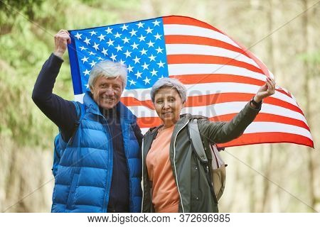 Waist Up Portrait Of Active Senior Couple Holding American Flag And Smiling At Camera While Enjoying