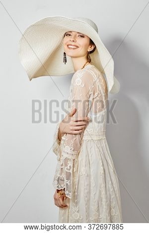 Portrait of a charming young woman in light elegant lace dress and a wide brim hat smiling happily at camera. Fashion shot, summer style. Happiness.