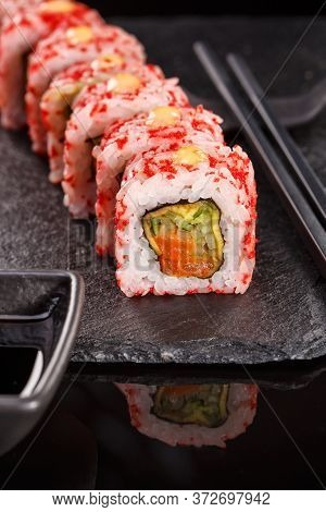 Rice Japanese Rolls Of Uramaki With Salmon And Cucumber Covered With Red Caviar.