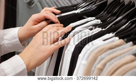 Female Hands Sorting Cotton Pullovers On A Hanger In A Clothing Store.