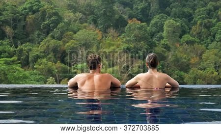 Young Couple Relaxes In Large Hotel Swimming Pool Blue Water Against Green Hilly Landscape Under Bri