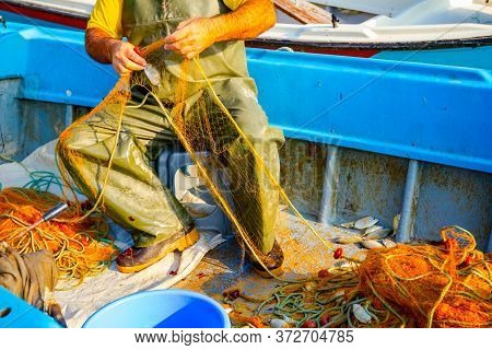 Fisher In Rubber Trousers And Boot Siting In His Boat And Pile Up Fishing Net For Angling At Open Se
