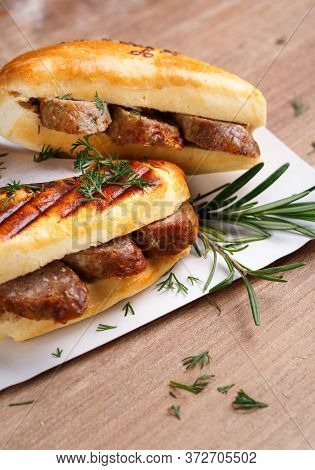 Blush Sandwiches With Sausages, Dill And A Sprig Of Basil On A White Plate On A Wooden Table. The Id