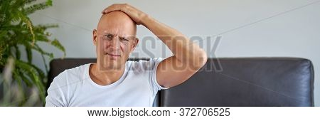 Feeling Depressed. Desperate Young Man Keeping His Hand On Forehead While Sitting On The Couch At Ho