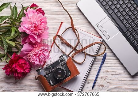 Flat Lay Womens Office Desk. Female Workspace With Laptop, Pink Peonies Bouquet, Camera And Coffee O