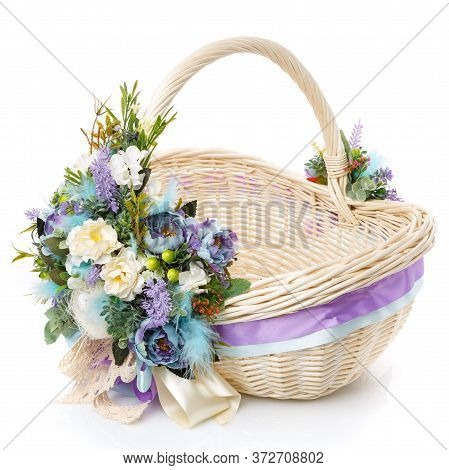 Brown Wicker Basket With Floral Decoration, Decorative Wooden Bunny And Ribbons On White Background.