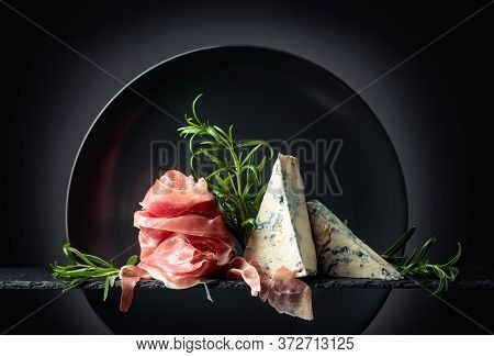 Traditional Mediterranean Snacks. Prosciutto Or Spanish Jamon With Blue Cheese And Rosemary.