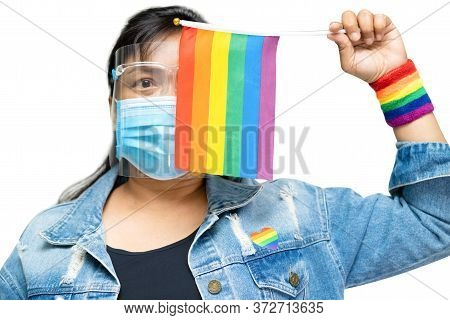 Asian Lady Wearing Blue Jean Jacket Or Denim Shirt And Holding Rainbow Color Flag, Symbol Of Lgbt Pr